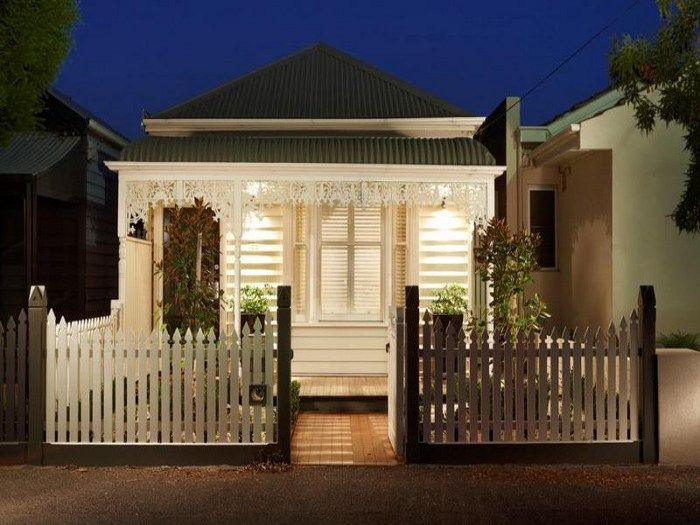 White on white Victorian cottage with a picket fence