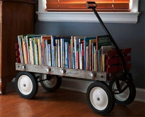 To keep books organized in a kid's room, use a cute red or wooden wagon.