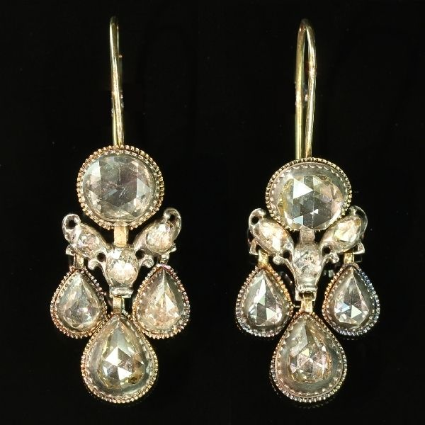 Top notch Baroque rose cut diamond ear jewels antique earrings. hree graduating teardrop shaped high domed rose cut diamonds surmounted by three rose cut diamonds diamonds in a V-shape with additional scrolling, attached to a larger round high domed rose cut diamond. The diamonds are set in a closed silver setting and the edges are decorated with a small lobed border. Circa 1659