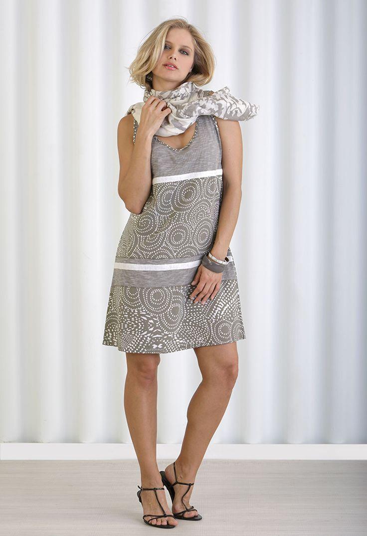 Vestido moderno corto sin mangas, cuello redondo y estampado geometrico. Con colgante a juego.
