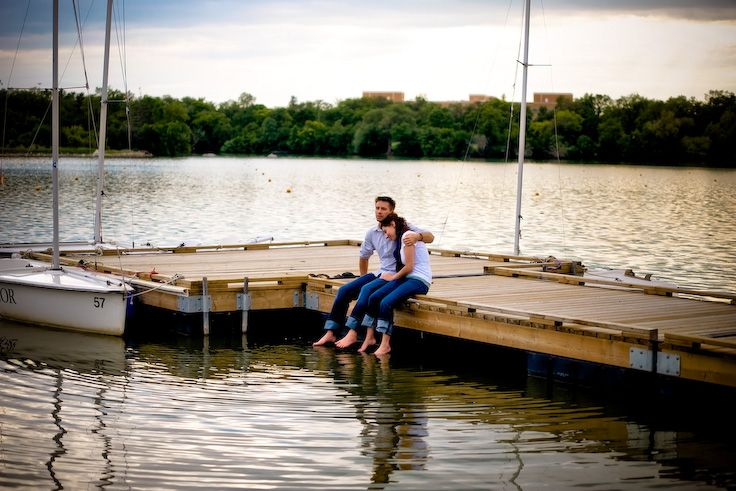 Regina, Saskatchewan Engagement Photography by Pure Photography & Design. Beautiful couple sitting on a dock cuddling while dipping feet in the water on a beautiful lake. www.purephotographyanddesign.com #reginaengagementphotography, #reginaengagementphotographer, #engagementphotographyideas, #reginaweddingphotographer, #reginaweddingphotography, #engagementphotography, #engagementpictures
