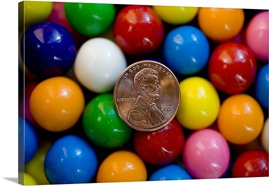 A penny backed by brightly colored gumballs as in penny candy ...