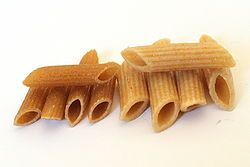 """Penne (Italian pronunciation: [ˈpenːe]) is a type of pasta with cylinder-shaped pieces. Penne is the plural form of the Italian penna, deriving from Latin penna (meaning """"feather"""" or """"quill""""), and is a cognate of the English word pen."""