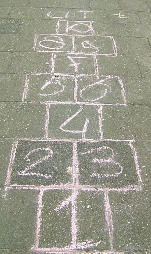 I spent hours playing hopscotch. When playing on the side walk, I used a small chain as my marker because it slid real good. When playing on dirt, I used just the right sized piece of broken glass because it would stick real good.