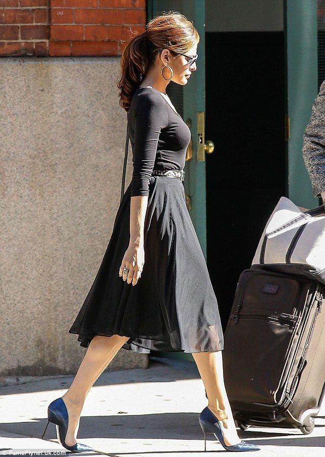 Eva Mendes shows off her curvy profile and toned gams as she hits the streets of New York in black A-line dress and blue stilettos
