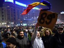 A man holds a placard highlighting the year dictator Nicolae Ceausescu was toppled from power