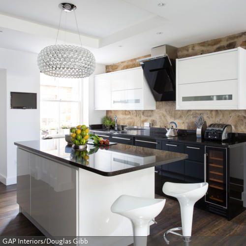 Bei der Retro-Küche mit Hochglanzfronten harmonieren vor allem die Farben Braun, Weiß und Schwarz wunderbar miteinander. Der runde Kristallleuchter ist ein weiterer…