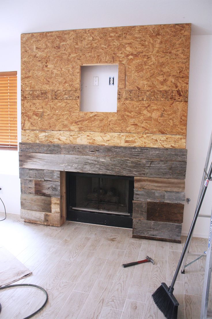 Step 6 - Using a table saw, measure + cut the reclaimed wood pieces to fit onto the front of the fireplace. Secure to the frame using a nail gun. Make sure to alternate the seams of the wood. You will want to use pieces of wood that are the same width all they way across each row. Also make sure to alternate the colors of the wood to create a great look.