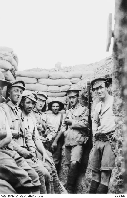 A group of unidentified Australian and New Zealand soldiers in a front line trench on the Gallipoli Peninsula. Standing in the narrow confines of a trench passage, with sandbags at the parapet above them, several of the men are smoking pipes and cigarettes. Australian War Memorial, C03420