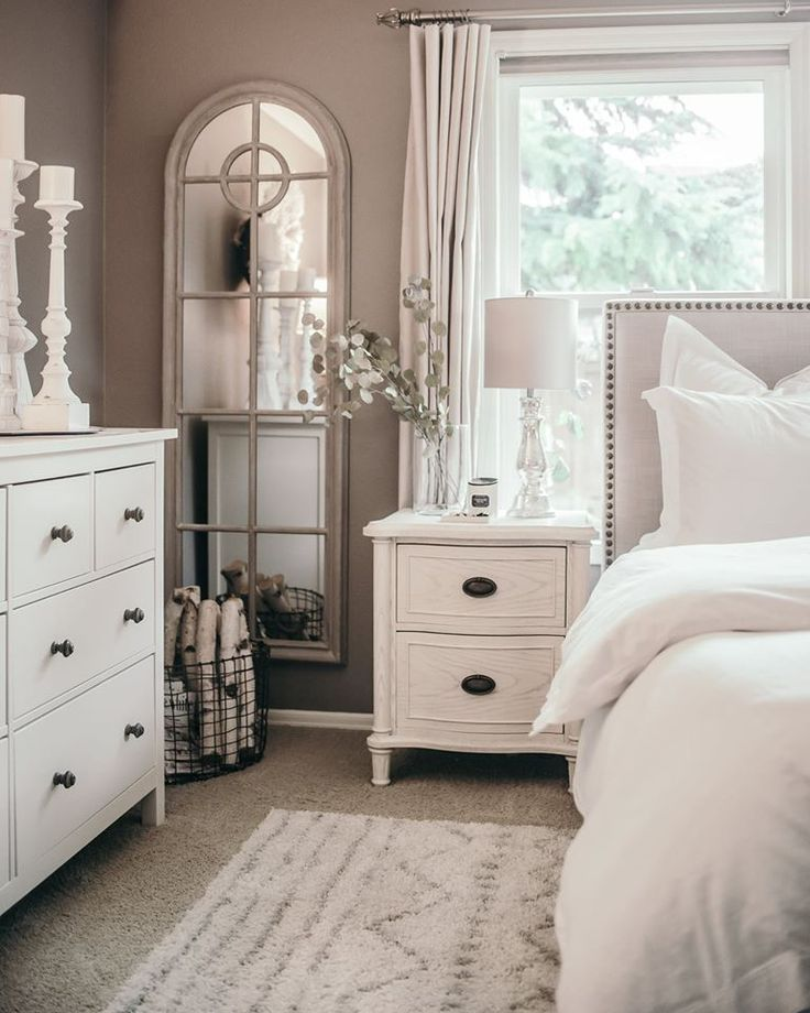 studded bed upholstery headboard, white bed table and dresser, glass mirror, white bed covers