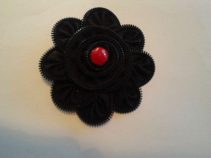Broche hecho con cremallera color negro, diente de plástico y bola en color rojo para dar un toque de color