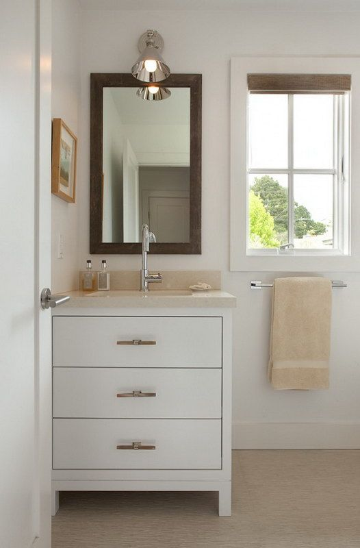a bathroom to the left is a white vanity with a brown framed mirror above
