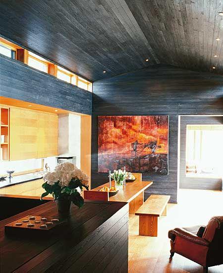 Også det enkle interiøret - tegnet av Beate Ellingsen - er inspirert av gammelbyggeskikk: Sengen som eget rom, langbordet og benken, peisen. Det er sortbeiset panel i de fleste rom. I dører, vinduer og tak er det valgt et lysere treverk som skaper lun kontrast til det sorte.