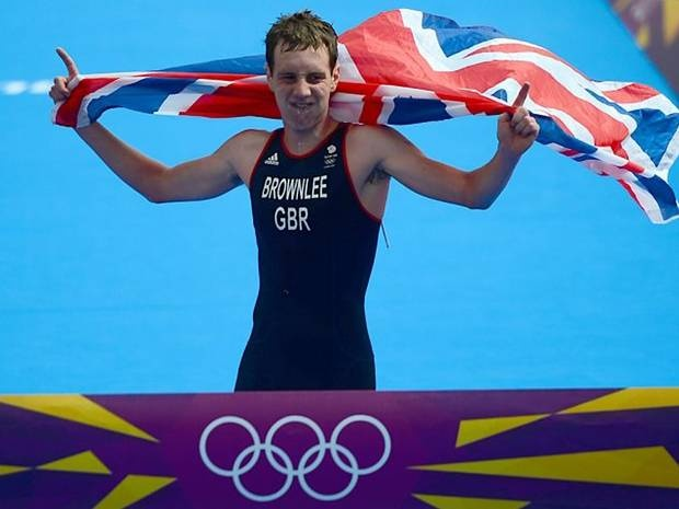 Gold medallist Britain's Alistair Brownlee celebrates while crossing the finish line to win the men's triathlon event at the London 2012 Olympic Games