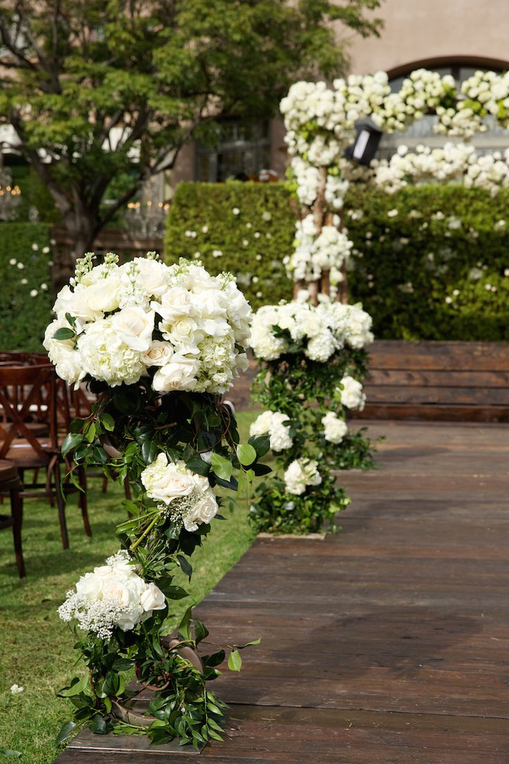 White floral adorned aisle markers looked beautiful at an outdoor wedding. #WeddingCeremony Photography: Bob & Dawn Davis Photography. Read More: https://www.insideweddings.com/weddings/ashley-hebert-and-jp-rosenbaum/438/