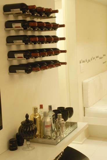 O suporte para vinhos é feito com pinos de aço inox, que foram fixos em painel de madeira. Ele comporta 25 garrafas. Como a moradora gosta de receber os amigos em casa, ela também tem uma bandeja da Zona D com outras bebidas preferidas.