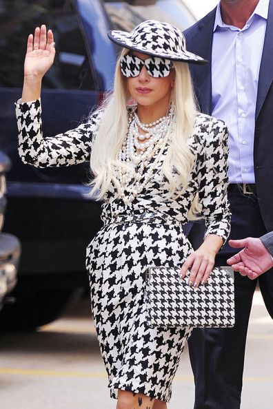 Lady Gaga completed her houndstooth ensemble with a patterned clutch from the same collection. Heavy pearls and opaque houndstooth shades completed her look.  Brand: Salvatore Ferragamo