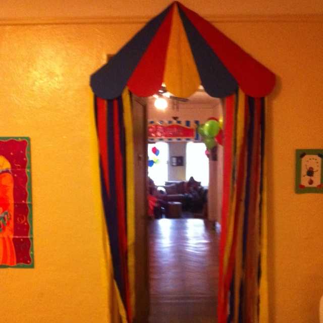 Carnival tent made from cardboard,  streamers and a little paint.  Idea for each doorway?
