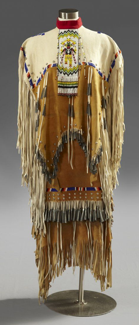 Apache Girl's Ceremonial Two Piece Puberty Dress, 20th c., composed of beaded hide with long fringe, with steel studs, conchos, and tin cones, consisting of a top and skirt, along with a beaded cravat and a pair of beaded hide boots, Top- H.- 32 in., Skirt- H.- 32in