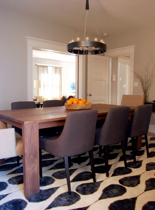 Contemporary, transitional dining room design for an urban bachelor. Patterned rug, upholstered dining chairs, contemporary chandelier. By Niche Interiors