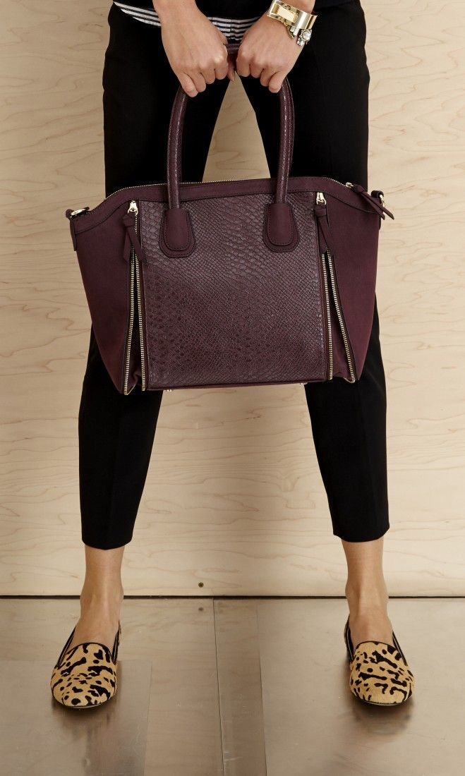 Structured satchel with faux snakeskin and zipper detailing. Includes top zipper closure.