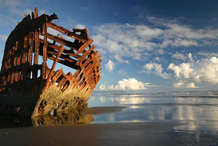 "Captain Lawrence's final toast to his ship, the Peter Iredale: ""May God bless you, and may your bones bleach in the sands."" Near Warrenton, Oregon, USA. Photograph by Matt Conwell."