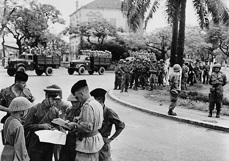 French and Viet Minh officers discuss the withdrawal of French colonial troops after the the Battle of Dien Bien Phu, 1954. After the battle and before the French left the country, the French soldiers were allowed to continue carrying their weapons.