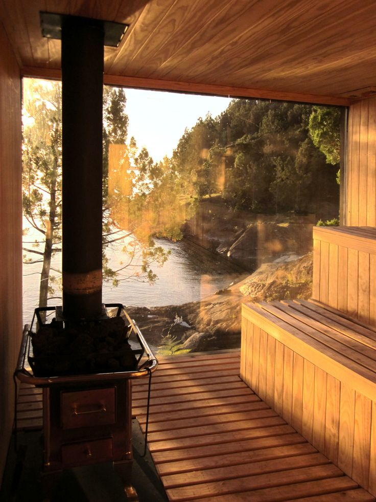 Encased with wood and glass, surrounded by trees and rocks, the sauna provides a relaxing hideaway for private lake front views.
