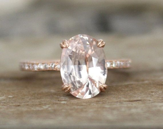 Hand milgrained 14K rose gold solitaire set diamond engagement ring featuring a natural oval brilliant cut peach champagne sapphire measuring 10.2 x