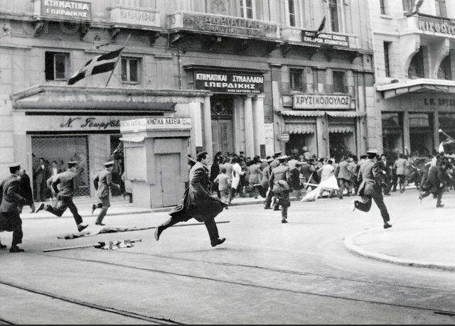 """Οδός Σταδίου. Αθήνα 1956. Στιγμιότυπο από την διαδήλωση ενάντια στην πολιτική που εφάρμοζαν οι Εγγλέζοι στην Κύπρο. Σε πρώτο πλάνο αστυνομικό εκσφενδονίζει πέτρα εναντίον των διαδηλωτών. """"Α police officer throwing a stone to the crowd during a demonstration against the British policy concerning Cyprus"""""""