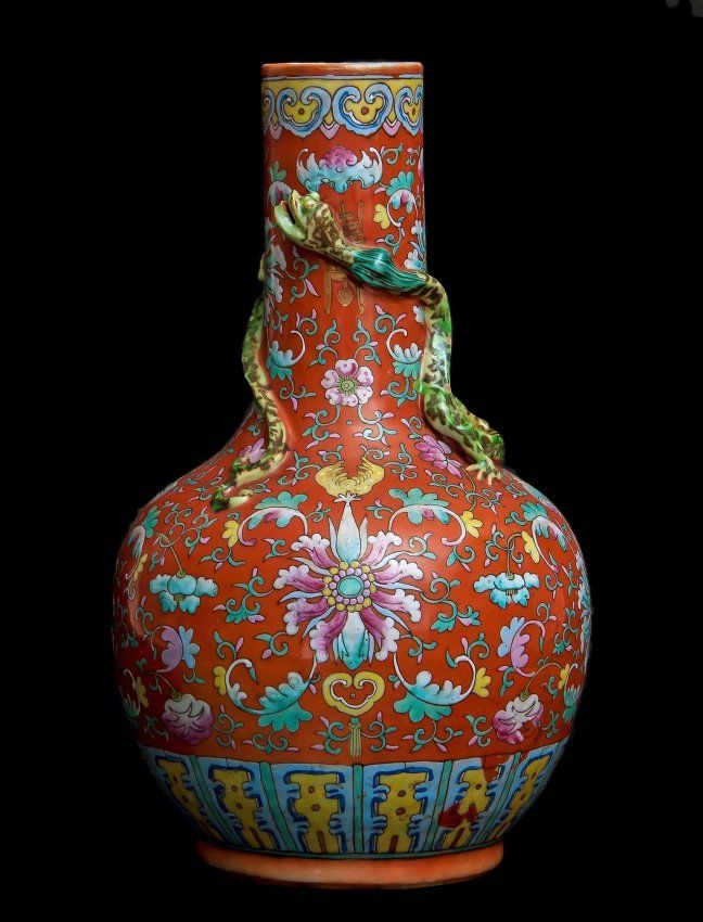 A Chinese famille rose , coral ground vase , 19th-early 20th century, the tall neck decorated with applied designs of an entwined chilong , densely painted on the turquoise ground with lotus flowers and peonies, wreathed by dense, curling foliage interspersed with pomegranates, citrus finger, between a border of yellow ground ruyi collaring the neck and multi-colored petal lappets encircling the foot, 36cm high