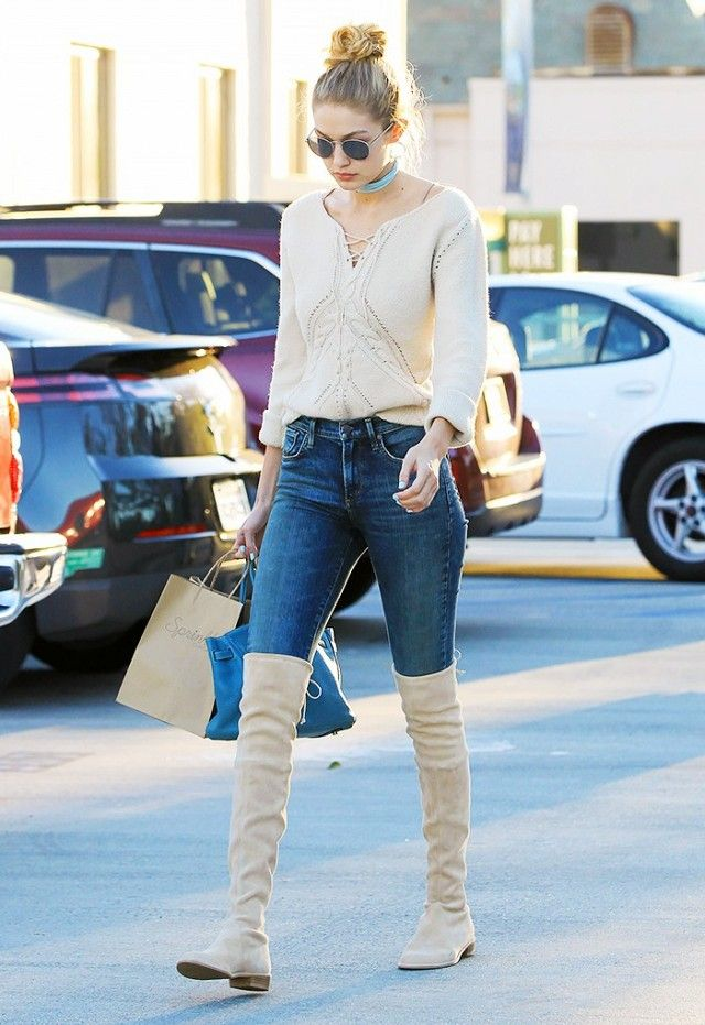 Gigi Hadid wears a skinny choker, lace-up sweater, skinny jeans, suede thigh-high boots, and a Birkin bag