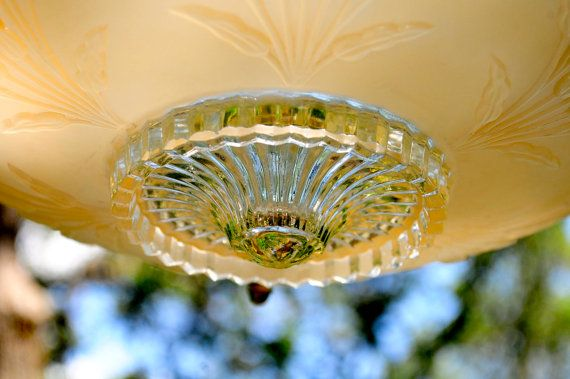This beige or peach Victorian glass bird feeder was created using a vintage light shade. The inside is smooth with a clear cut glass center bottom. The outside of the bird feeder has a delicate raised wheat pattern and a symmetrical pattern on the bottom. The rim is clear cut glass with