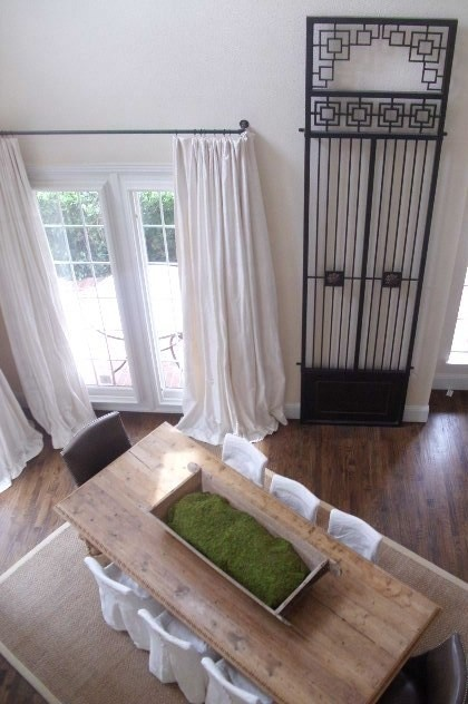 Look at that huge wrought iron gate... Isn't that just gorgeous?! Also love the floor, the clean and elegant window treatments and the moss-in-a-trough-centerpiece. Great to turn the table on a angle