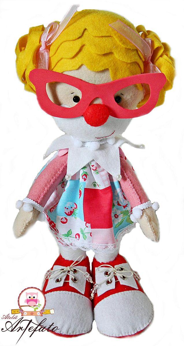 O Ateliê Artefato traz para você uma linha de bonecos da turma do circo para decorar a sua festa ou seu cantinho preferido!! <br> <br>Boneca Palhacinha: feito em feltro, toda costurado à mão, com enchimento em fibra de silicone, detalhes em miçangas, fita, tecido, EVA, meia pérolas e botões e suporte interno em arame, para que ela se sustente sozinha em pé. Possui braços articuláveis e um lindo óculos em EVA dando um toque super especial e descolado a bonequinha. <br> <br>Ideal para a…