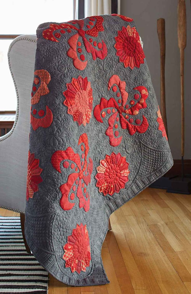 Appliqué quilt patterns can be quite stunning, like Red Galaxy by Randy McCarty! Machine or hand stitch red appliqués on a charcoal background for this dramatic throw quilt pattern. Use a variety of red prints to add interest and texture.