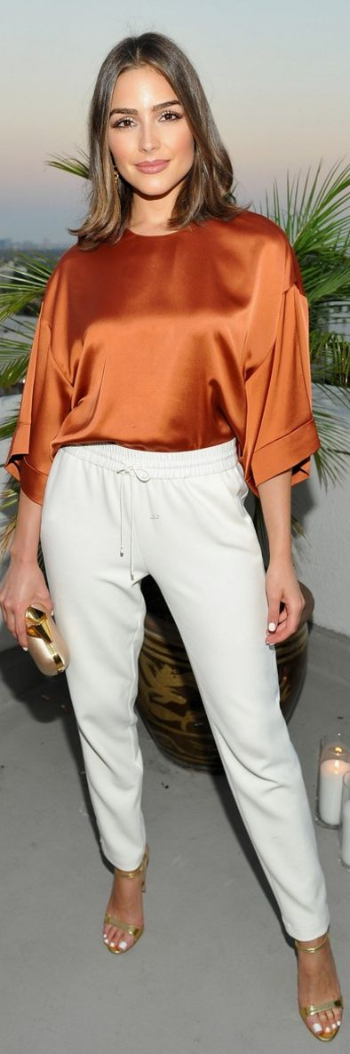 Who made Olivia Culpo's white pants, orange top, and gold jewelry? (OutfitID)