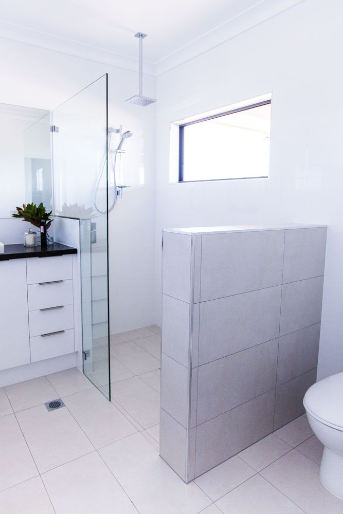 A half height wall has been used in this ensuite to allow light to filter into the room from the window in the shower area whilst still keeping the toilet in a separate zone. A simple piece of frameless glass with no pivot door continues to allow for good lighting, which is important in wet areas. - Shepperd Building Company