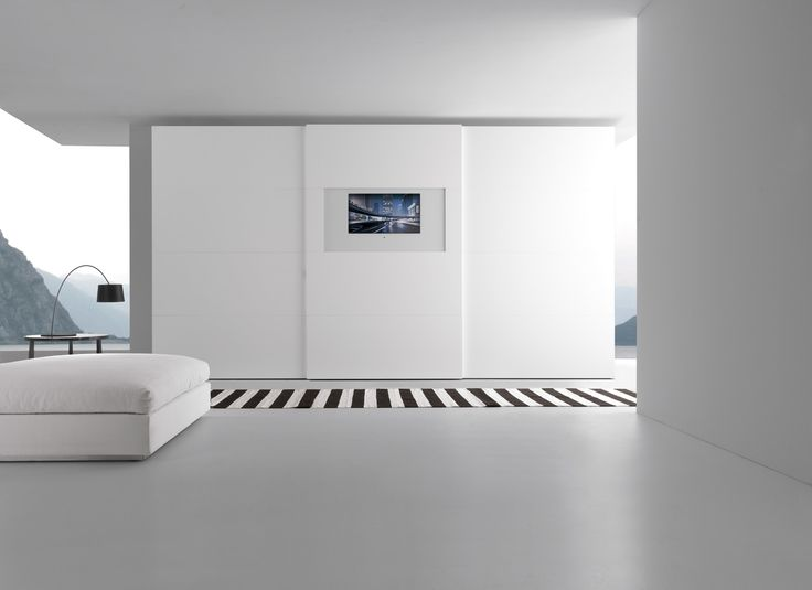 Wardrobe with Dama sliding door and central, projecting Dama_tv integrated door with matt bianco candido lacquered panels and panels with bianco lacquered glass specifi c for the TV; the wide side frames are in gloss bianco candido lacquer.__ Armadio con anta scorrevole Dama e al centro sporgente Dama_tv integrated, con pannelli laccato opaco bianco candido e pannelli con vetro colorato bianco speciale per tv, le cornici laterali sono laccate opaco bianco candido.