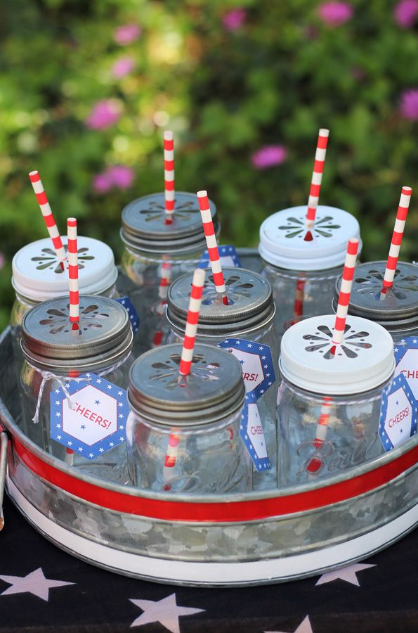 "The last time I was at a vintage flea market, I was able to pick up an old ironing board, a large flag-inspired scarf and a hand embroidered ""Drinks"" banner, all of which made up my drink station. Adults drank tea, lemonade and punch in mason jar glasses and the kids used their patriotic-colored cups. Water bottles with custom labels and some all-American cola in the vintage bottles finished off the drinks. Evite-Party-Ideas-Contributor-Sweet-Jelly-Party-4th-of-July-mason-jars"