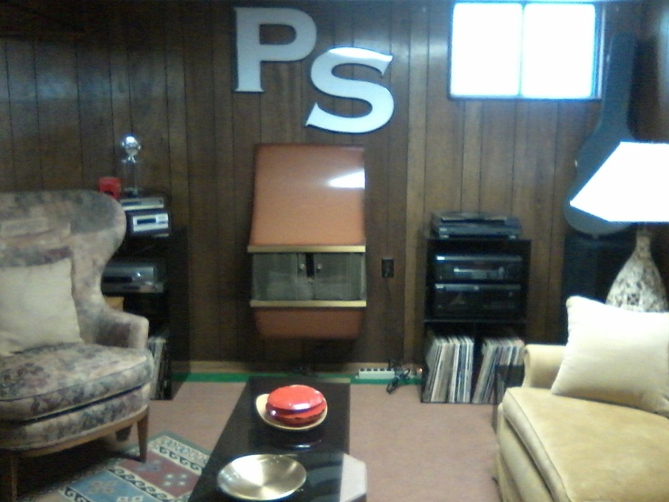 """Welcome to the """"PS Lounge,"""" a comfy basement getaway, complete with a wall-mounted 1960s electric fireplace heater. The coffee table, end tables, and media shelves are 1970s smoke gray plexiglass - another estate sale find."""