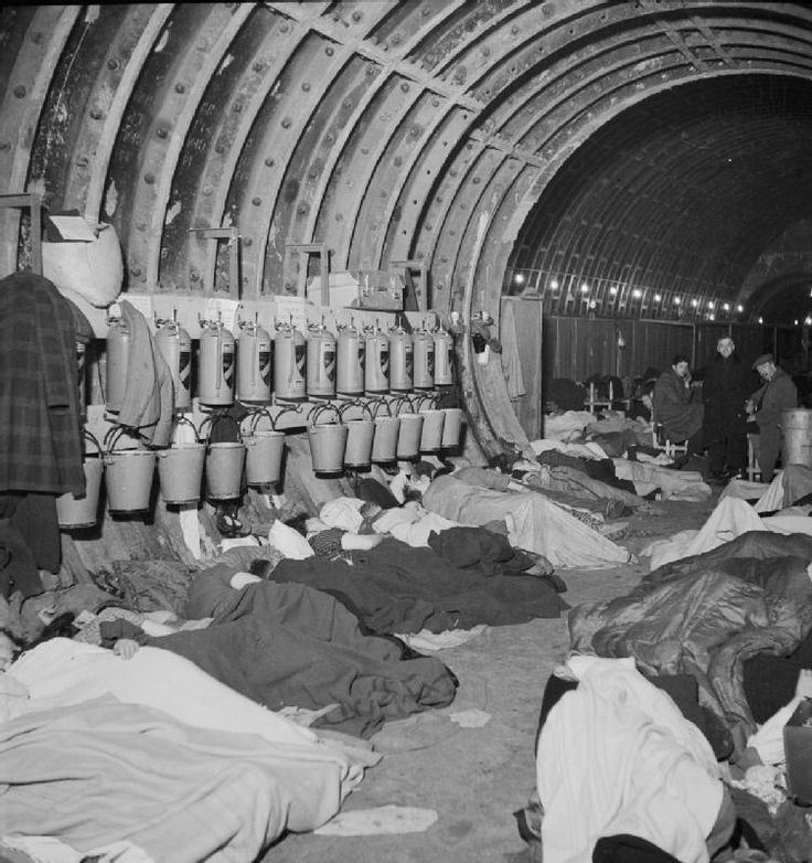 London, November 1940: Liverpool Street Underground Station Shelter. Londoners sleep under a row of sand buckets and fire extinguishers suspended from the underground tunnel wall.
