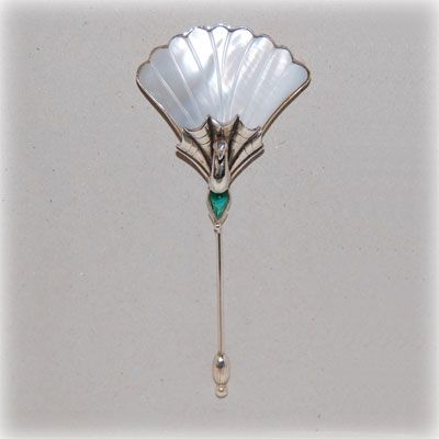 Peackock brooch with mother of pearl, an emerald colored crystal and handmade sterling silver details and setting. Made in our workshop.