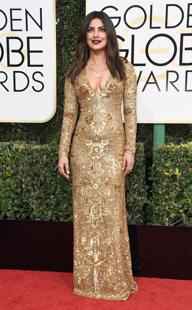 2017 Golden Globes: Priyanka Chopra is wearing a gold embellished Ralph Lauren long sleeve gown with a deep neckline. I'm always excited to see Priyanka on the red carpet because she always stuns! Best dressed choice!