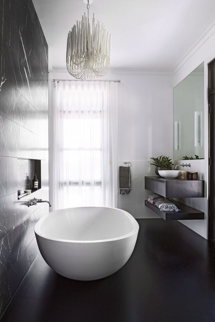 **Light and dark.** A freestanding bath with luxurious rounded edges, combined with a contemporary chandelier and monochrome palette make for a truly show-stopping bathroom space. *Photo: Angelita Bonetti / bauersyndication.com.au*