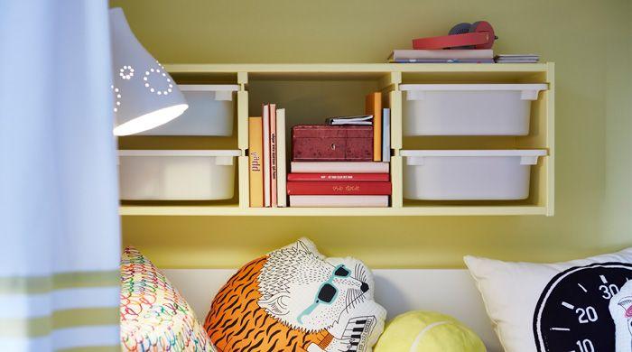 Ei seng og gulmalt veggoppbevaring for barnerom mot en gul vegg