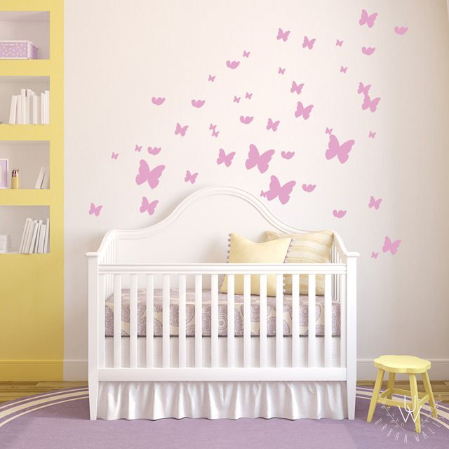 Various sized vinyl pink butterfly wall stickers placed on a beige wall behind a white crib in a girl's nursery.