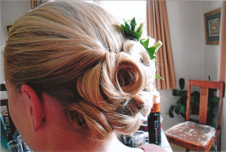 Smooth curls twisted up into a low sculptured bun. www.sharynbutters.co.nz