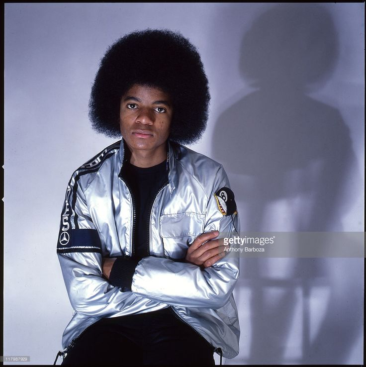 Portrait of singer Michael Jackson (1958 - 2009), dressed in a shiny silver jacket, and with arms crossed in November 1977.