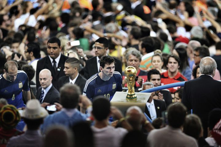 The 1st prize in the Sports Singles category of the 2015 World Press Photo Contest by Bao Tailiang, China, for Chengdu Economic Daily shows Argentina player Lionel Messi looks at the World Cup trophy during the final celebrations at Maracana Stadium in Rio de Janeiro, Brazil on July 14, 2014. Argentina were defeated by Germany in the final. (AP Photo/Bao Tailiang, Chengdu Economic Daily)